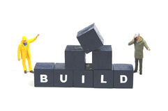 Build. Two workmen standing next to the word build stock image