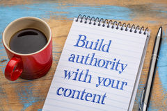 Build authority with your content. Blogging tip - handwriting in a spiral notebook with a cup of coffee stock images