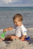 Build on the beach. A little caucasian   baby boy in the face the sea playing with her toys on the beach on a summer day Royalty Free Stock Image