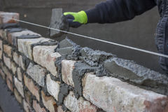 Build a brick wall, bricklaying spreading a bed joint. Bricklaying foundation walls, spread a mortar bed joint for building brick. Brick mason laying old brick Royalty Free Stock Photo