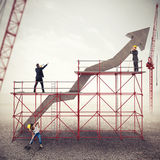 Build a business success. Mixed media. Teamwork builds an arrow uphill under construction. Build a business success. Mixed media royalty free stock images