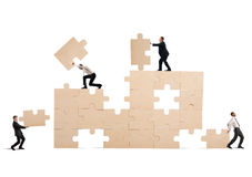Build the business. Team of businessmen collaborate and cooperate to build a puzzle Royalty Free Stock Image