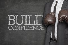 Build confidence on blackboard with businessman. Wearing boxing gloves stock photography