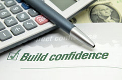 Build confidence printed on book. With calculator and pen royalty free stock images