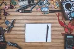 Build drone parts. Assembly drone accessories quadcopter on wooden background, notebook with pen place for advertising and labels Royalty Free Stock Photos