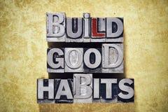 Build good habits. Phrase made from metallic letterpress type on grunge cardboard background Stock Photos