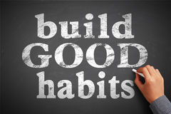Build Good Habits. Hand with chalk is writing the concept of Build Good Habits on the blackboard stock image