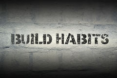 Build habits GR. Build habits stencil print on the grunge white brick wall Royalty Free Stock Image