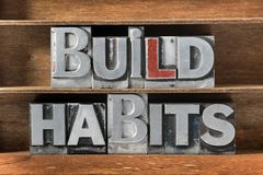 Build habits tray. Build habits phrase made from metallic letterpress type on wooden tray Royalty Free Stock Photo