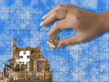 Build the house. Hand bring piece of house (puzzle Royalty Free Stock Photography