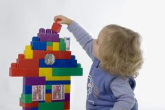 Build a house. Child build a house with playstones,decorate with banknotes stock image