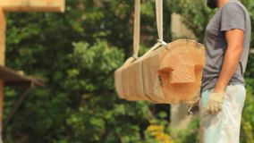Build a house from logs. A log is hoisted with a crane to build a house stock video footage
