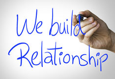 We build relationship hand writing on blue marker on transparent wipe board.  royalty free stock photo