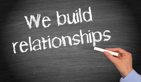 We build relationships - female hand with chalk writing text. On chalkboard or blackboard Stock Images