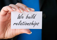 We build relationships. Text ' We build relationships' written on a small white card closeup held in a woman's hand, black and blue background Stock Photo