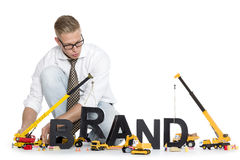 Brand start up: Businessman building brand-word. Royalty Free Stock Photos
