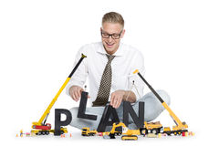 Build up a plan: Businessman building plan-word. Stock Photos
