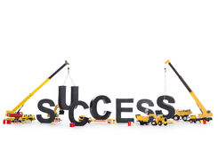 Build up success: Machines building success-word. Build up success concept: Black alphabetic letters forming the word success being set up by group of Royalty Free Stock Photos