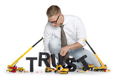 Build up trust: Businessman building trust-word. Build up trust concept: Focused businessman building the word trust along with construction machines, isolated Royalty Free Stock Photos