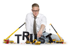 Build up trust: Businessman building trust-word. Build up trust concept: Friendly businessman building the word trust along with construction machines, isolated Stock Photo