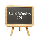 Build Wealth 101. A chalkboard presenting the words build wealth 101 Stock Photography