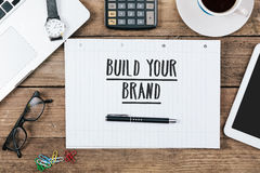 Build you brand on notebook on Office desk with computer technol. Words Build your brand on notebook, Office desk with electronic devices, computer and paper royalty free stock images