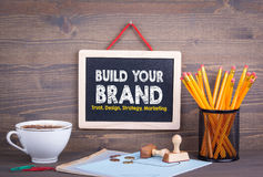 Build Your Brand concept. Trust Design Strategy Marketing. Chalkboard on a wooden background.  royalty free stock photos