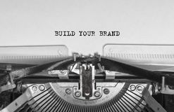 BUILD YOUR BRAND typed words on a vintage typewriter. BUILD YOUR BRAND printed the words on a typewriter. advertising. finance. business. words on paper stock photos