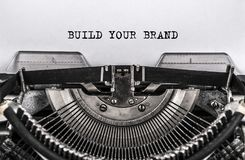 BUILD YOUR BRAND typed words on old vintage typewriter. close up. BUILD YOUR BRAND printed the words on an old vintage typewriter. close.financial. advertising stock photos