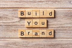 BUILD YOUR BRAND word written on wood block. BUILD YOUR BRAND text on table, concept.  stock image