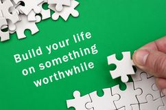 Build your life on something worthwhile. The hand folds a white. Jigsaw puzzle and a pile of uncombed puzzle pieces lies against the background of the green Stock Images