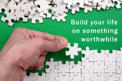 Build your life on something worthwhile. The hand folds a white. Jigsaw puzzle and a pile of uncombed puzzle pieces lies against the background of the green Royalty Free Stock Photography