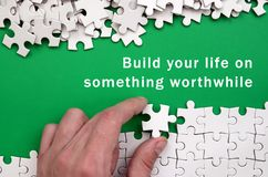 Build your life on something worthwhile. The hand folds a white. Jigsaw puzzle and a pile of uncombed puzzle pieces lies against the background of the green royalty free stock photo