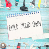 Build your own against tools and notepad on wooden background Royalty Free Stock Photo