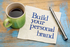 Build your personal brand advice. Handwriting on a napkin with a cup of espresso coffee royalty free stock photo