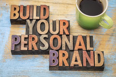 Build your personal brand. Motivational concept in vintage letterpress wood type block with a cup of coffee stock image