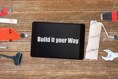 Build it your way against tools and tablet on wooden background Stock Image