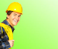 Builder. Handsome builder in yellow uniform. Over green  background Royalty Free Stock Photo
