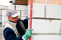 Builder. At work, checking level of new wall Royalty Free Stock Photos