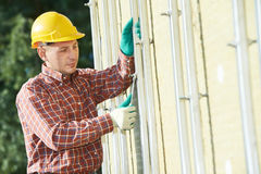 Builder at aerated facade tile installation Royalty Free Stock Images