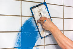 Builder applying colorful blue grouting Stock Image