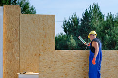 Builder applying glue to a wooden wall panel Stock Photo