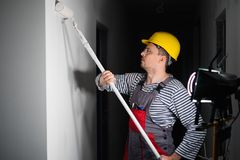 Builder applying paint on a wall Royalty Free Stock Images