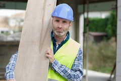 Builder and apprentice carrying wood on construction site. Man royalty free stock images