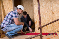 Builder and Architect Inspecting Building Doorway. Builder and Architect Working Together and Inspecting Even Level of New Home Doorway Inside Building Royalty Free Stock Images