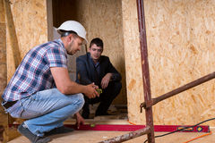 Builder and Architect Inspecting Building Doorway. Builder and Architect Working Together and Inspecting Even Level of New Home Doorway Inside Building Stock Photo