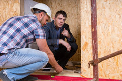 Builder and Architect Inspecting Building Doorway. Builder and Architect Working Together and Inspecting Measurement of New Home Doorway Inside Building Royalty Free Stock Photo