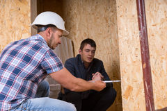 Builder and Architect Inspecting Building Doorway. Builder and Architect Working Together and Inspecting Measurement of New Home Doorway Inside Building Royalty Free Stock Photography