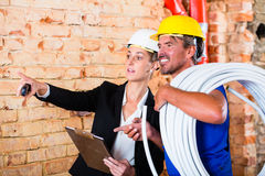 Builder and architect working on construction site Stock Photography