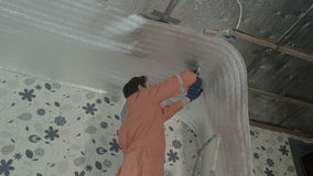 Builder attaches vapor barrier to wooden beams on the ceiling stock video